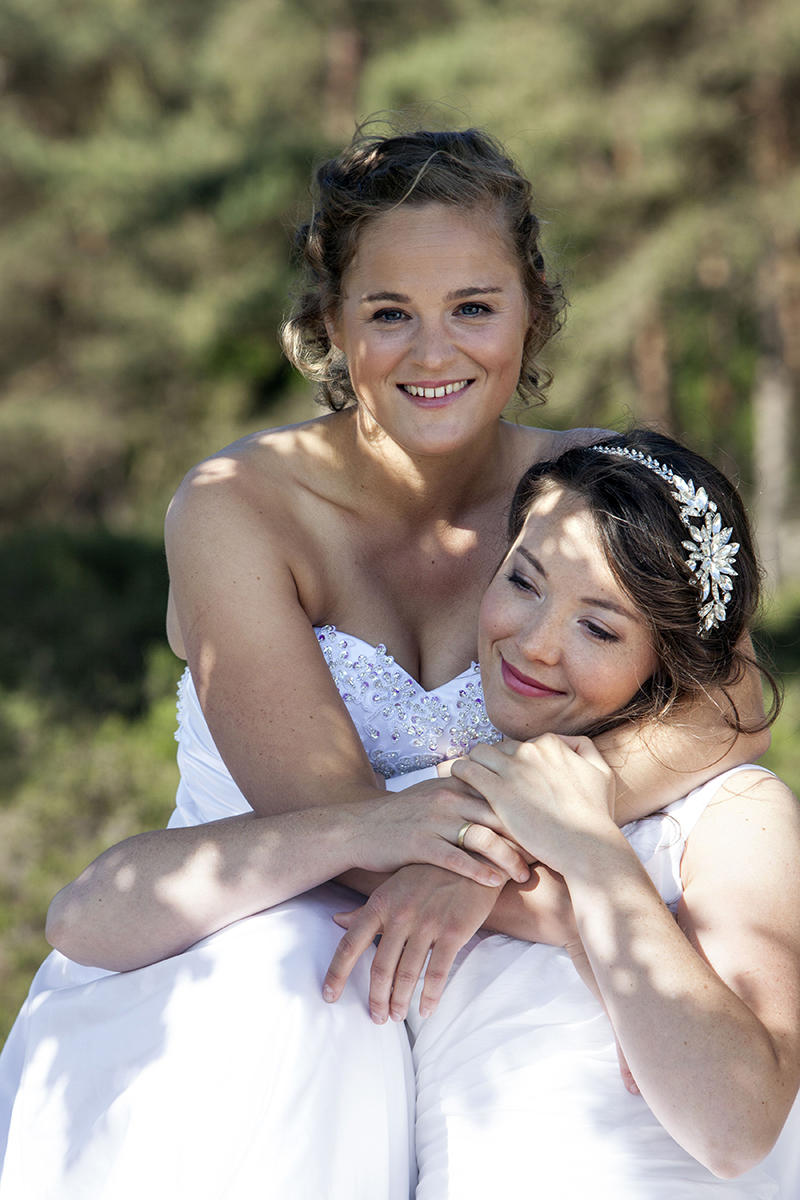 two brides smile and embrace in nature surroundings