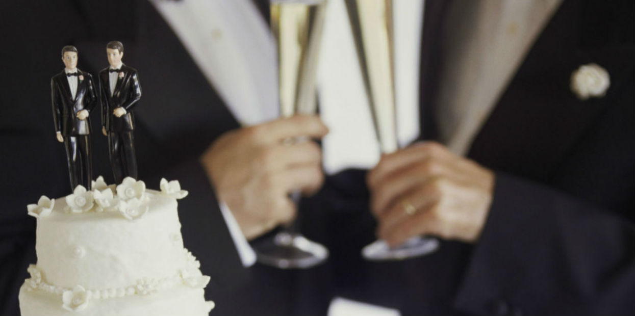 male wedding couple ontop of cake