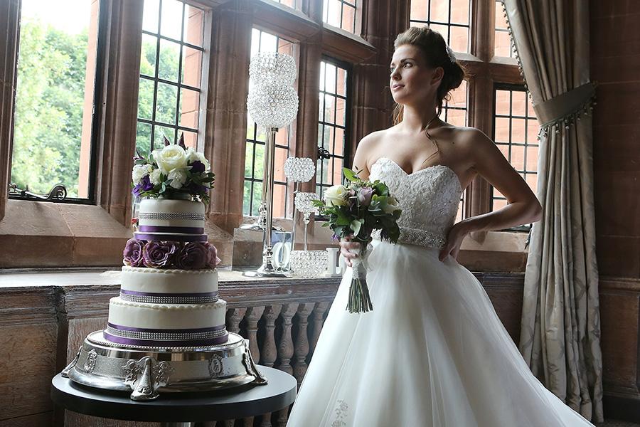 Wedding posing next to wedding cake