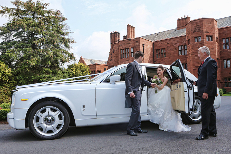 Groom helping bride out of white car