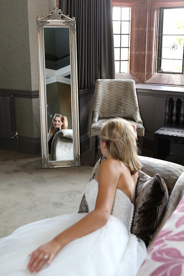 Bride in dress laying on chaise lounge sofa with mirror