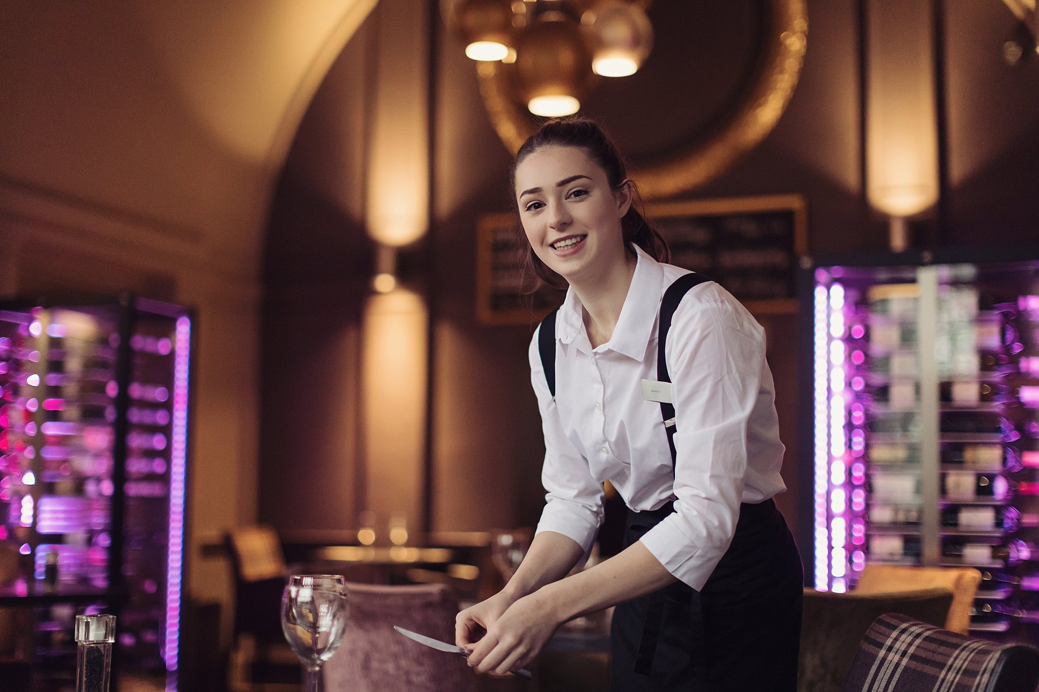 Waitress smiling whilst setting table