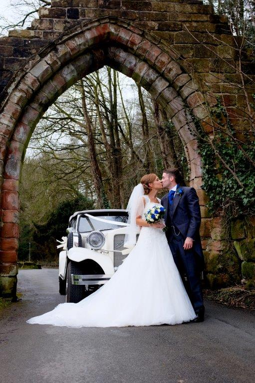 Wedding couple kissing under arch