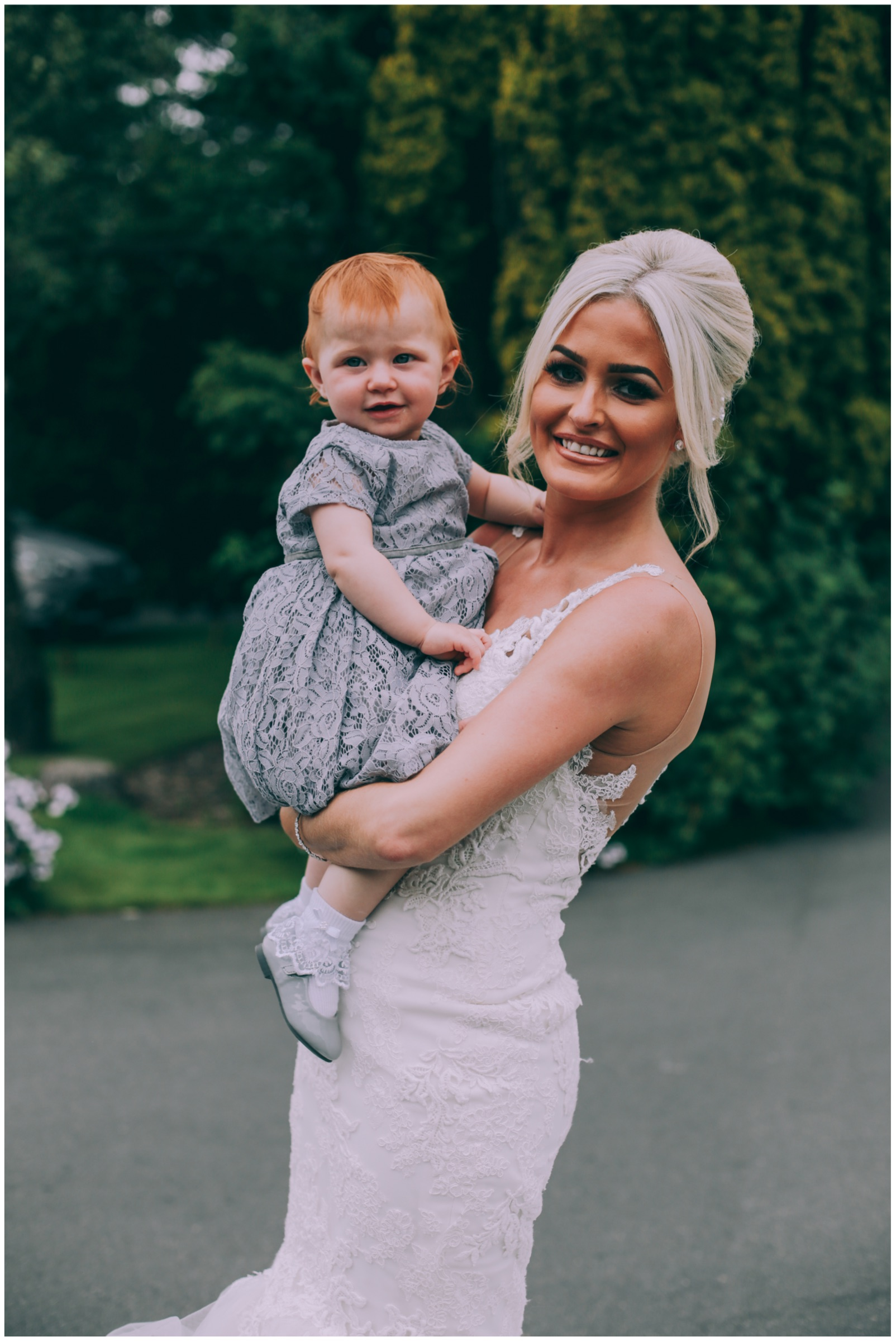 Bride in mermaid wedding dress with child