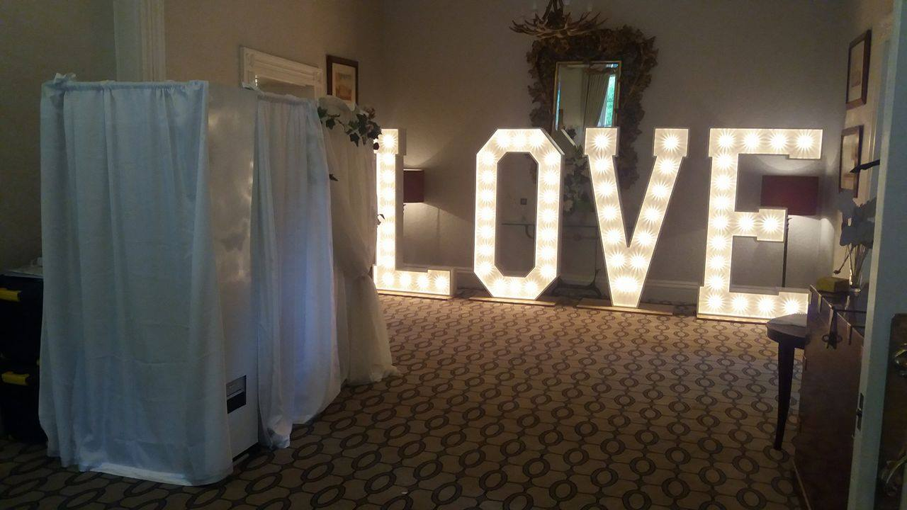 Wedding photo booth with illuminated LOVE sign behind