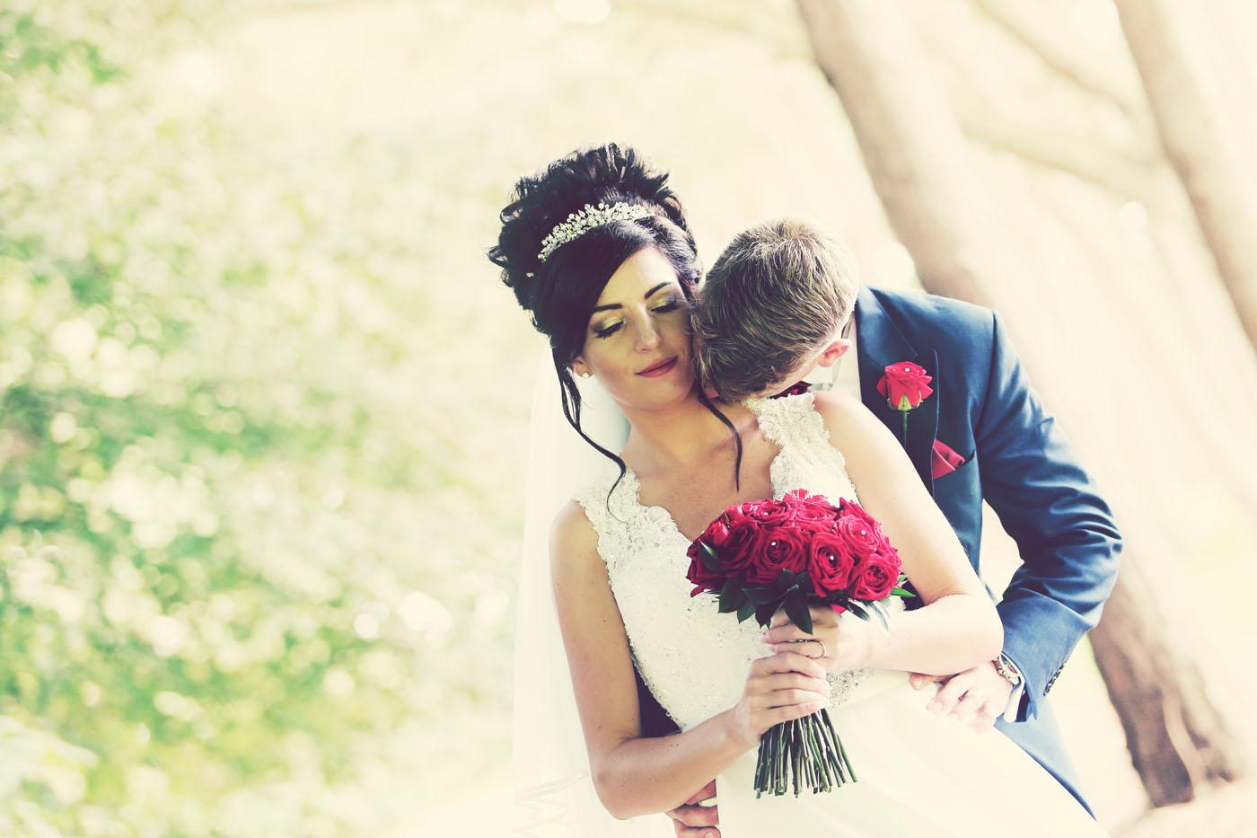 groom kissing bride on neck