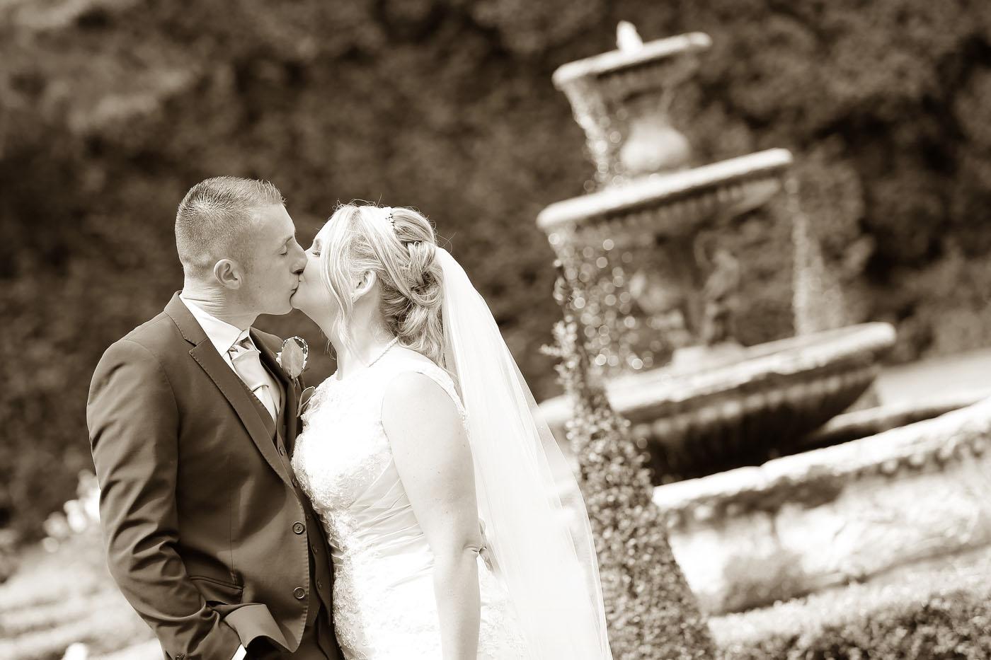 Couple kissing next to fountain