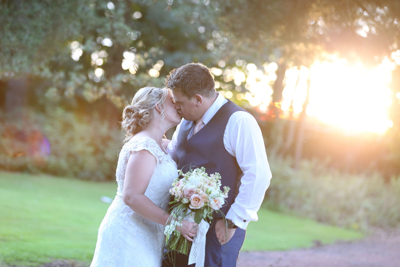 Bride and groom kissing infront of sunset