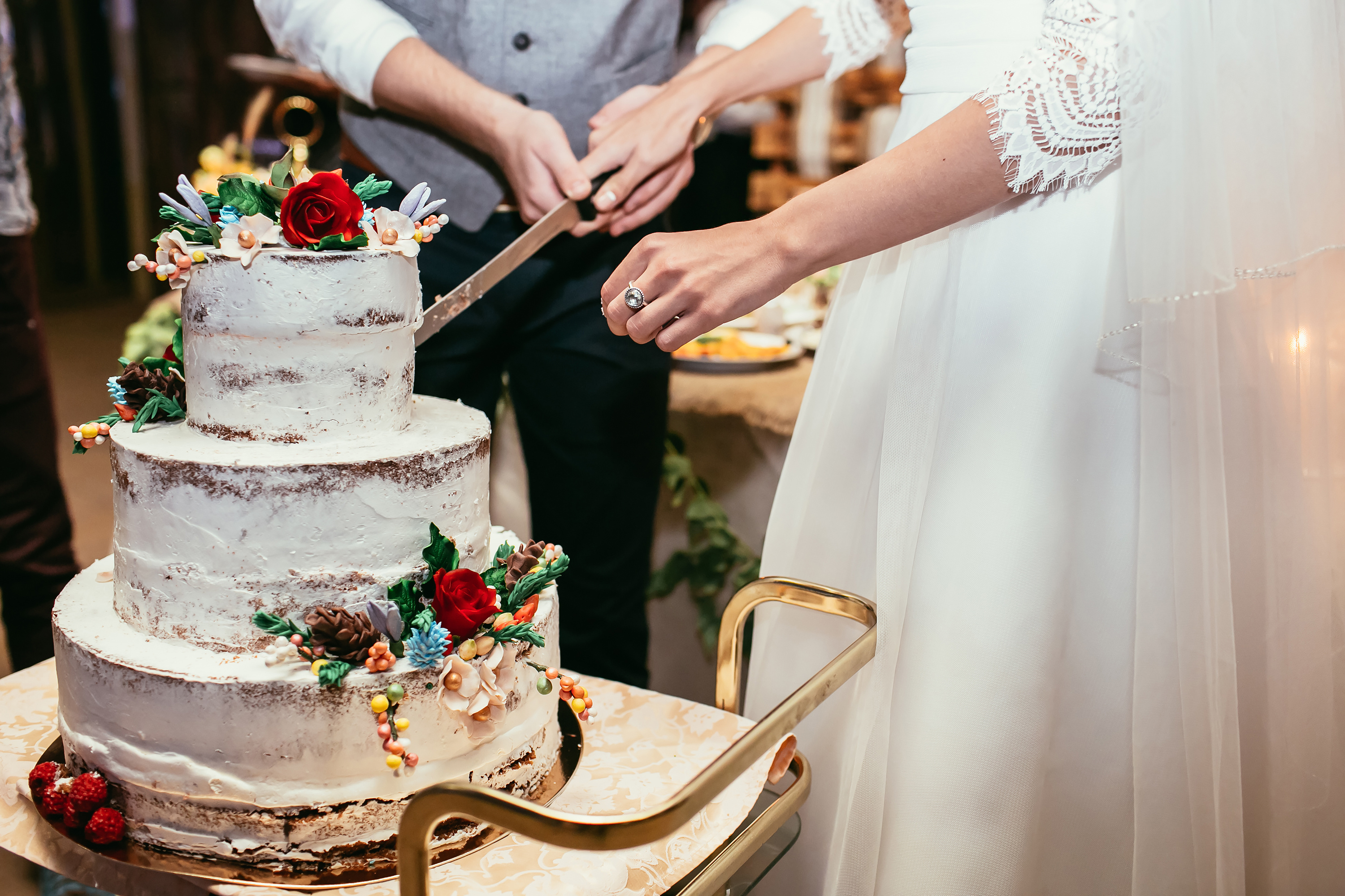 bride and groom cut rustic wedding cake on wedding banquet with